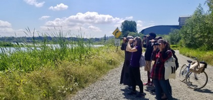 Olivia leading a group of high school students on a birding trip